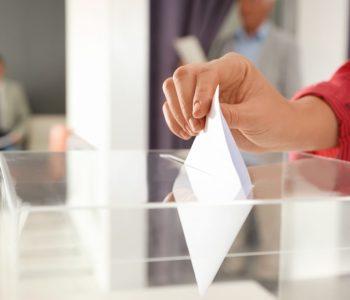 Woman putting ballot paper into box at polling station, closeup