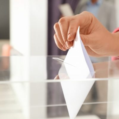 Woman putting ballot paper into box at polling station, closeup